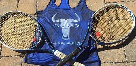 "Two tennis rackets and a shirt with a wildebeest head and caption ""Some beauty. All beest."""